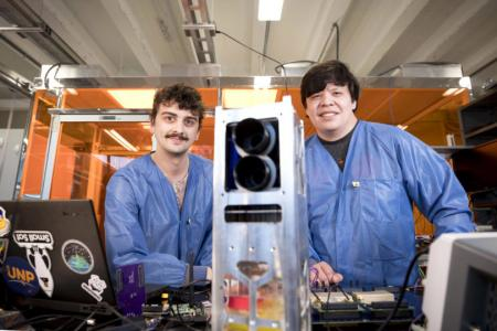 Two students pose with their satellite in the Small Satellite Research Laboratory, which was founded in 2016 with the original goal of building a spacecraft.  Courtesy Dorothy Kozlowski